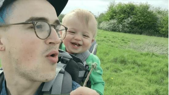 タンポポを吹く父親と、それを見て喜ぶ赤ちゃん
