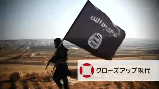 「イスラム国」の国旗を風になびかせて歩く男性/クローズアップ現代
