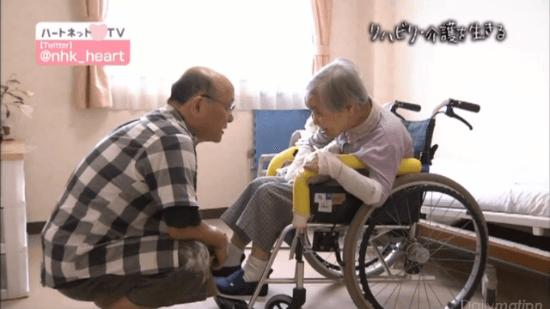 車椅子に座る認知症の母に寄り添う岡野さん